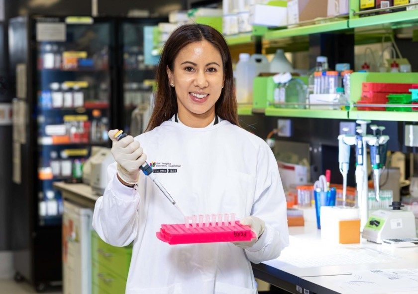 Woman in lab holding lab equipment smiling at camear